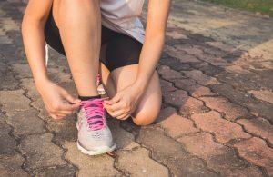 una chica atándose las zapatillas de correr