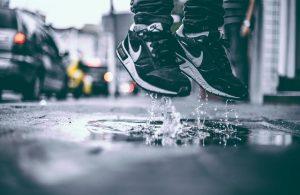 unos pies con zapatillas saltan sobre un charco de agua